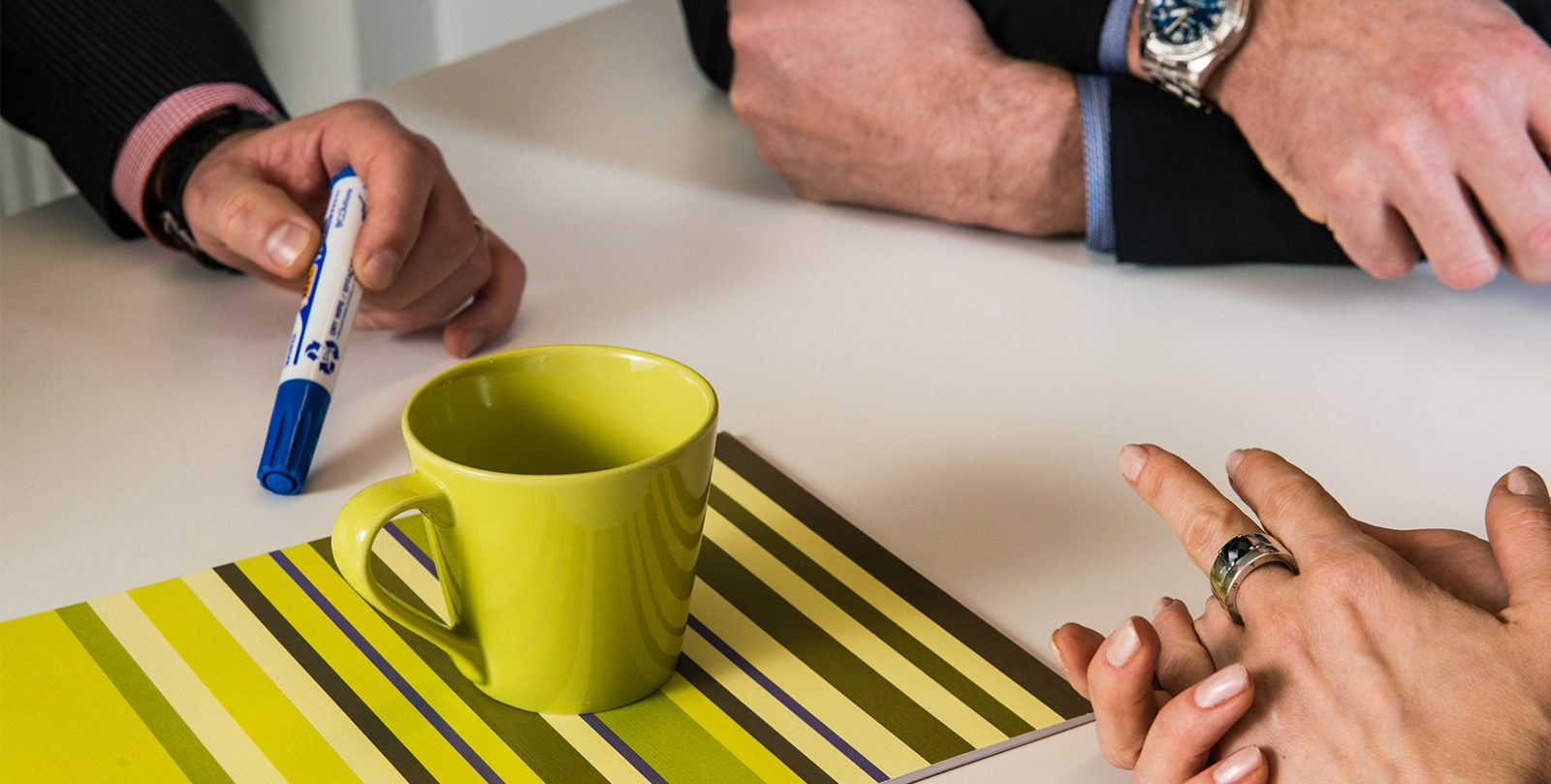 Hands on a table width a green cup